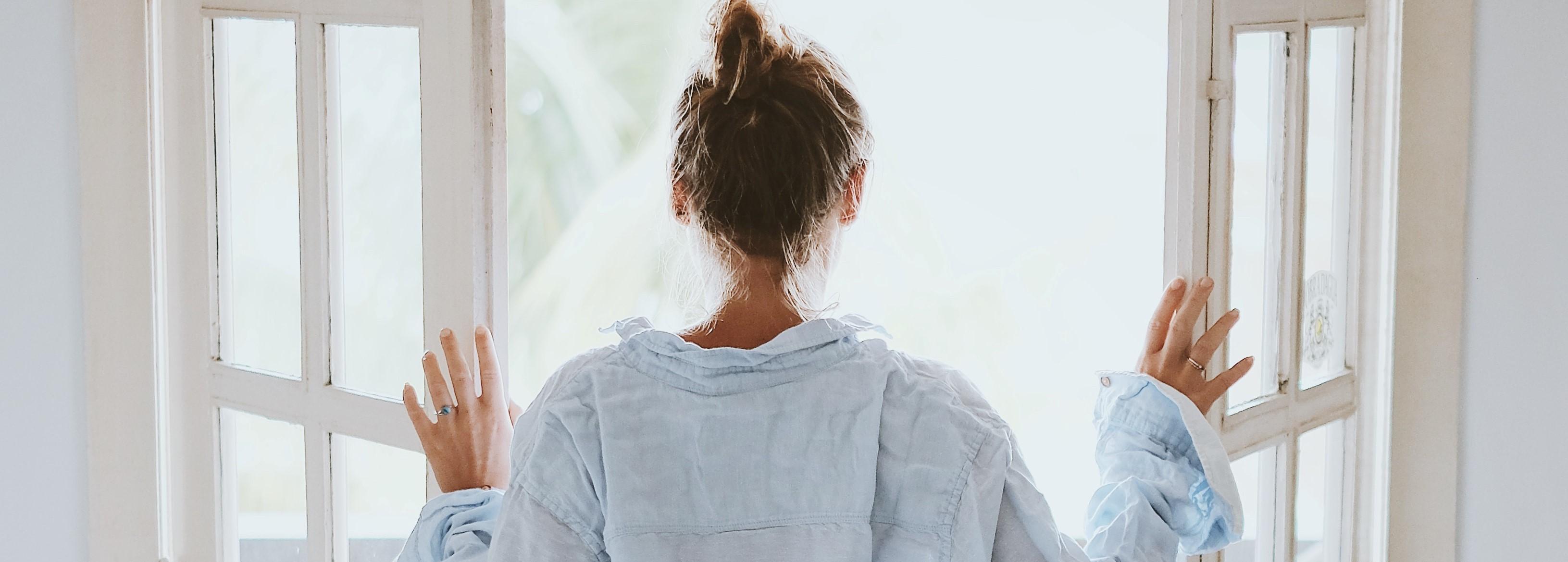 Frau sucht Physiotherapie schaut aus dem Fenster.